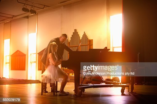 Caucasian music teacher and student at piano