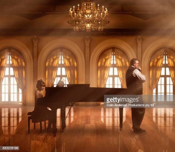 Caucasian music teacher listening to student at piano in ballroom