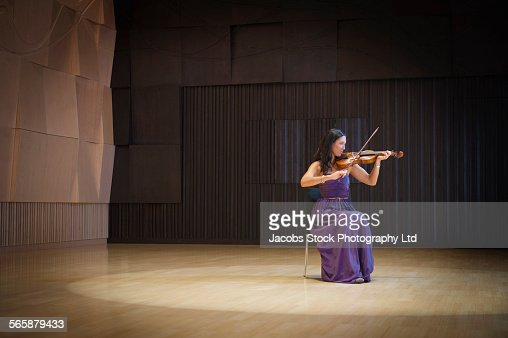 Caucasian musician playing violin on stage