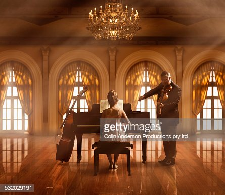Caucasian musicians playing piano and violin