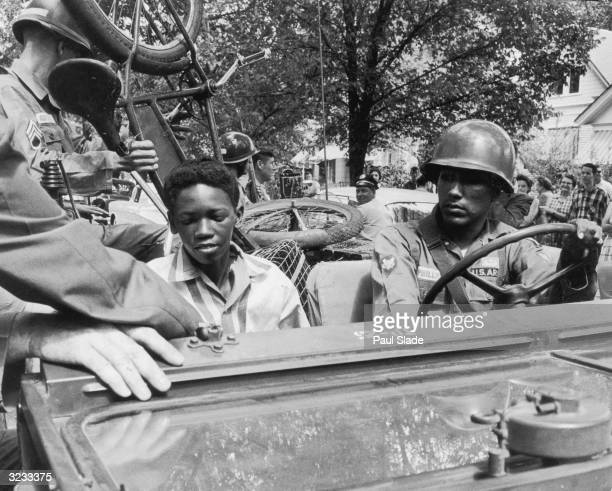 Caucasian National Guardsmen give an AfricanAmerican student and his bicycle a lift to school while enforcing desegregation at Central High School in...