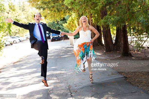 Caucasian newlywed couple skipping on road