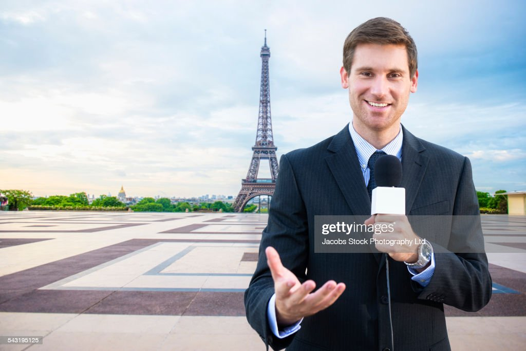 Caucasian news reporter talking near Eiffel Tower, Paris, France