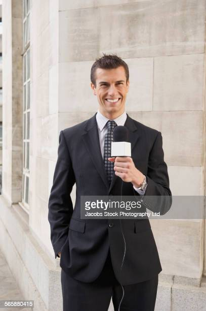 Caucasian newscaster holding microphone outside building
