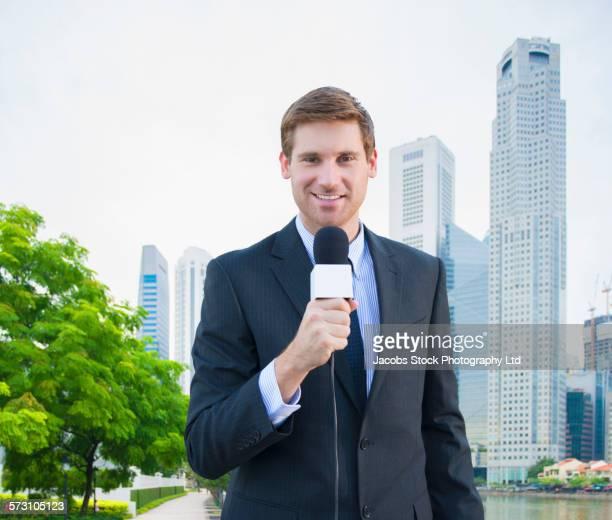 Caucasian newscaster reporting in Singapore cityscape