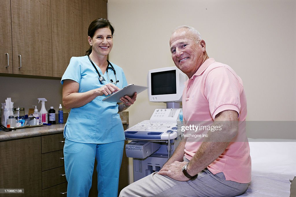 Caucasian nurse and patient smiling in office : Stock Photo