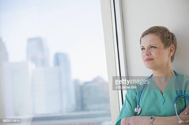 Caucasian nurse near window