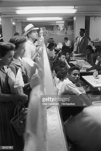 Caucasian onlookers peer over a railing while watching AfricanAmerican protesters during their sitin at Brown's Basement Luncheonette Oklahoma