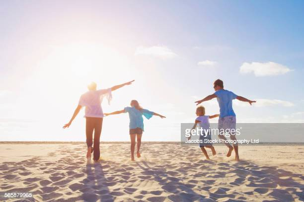 Caucasian parents and children playing airplane on beach