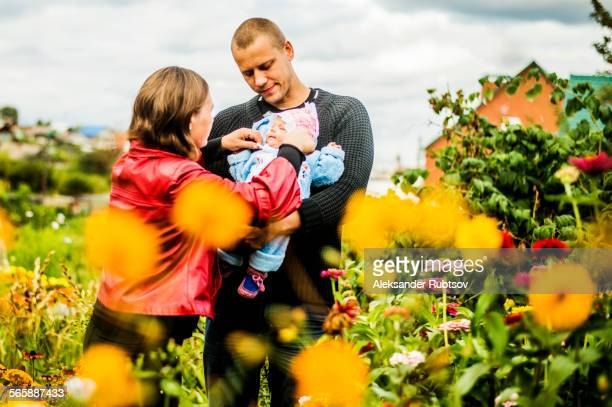 Caucasian parents holding baby near flowers