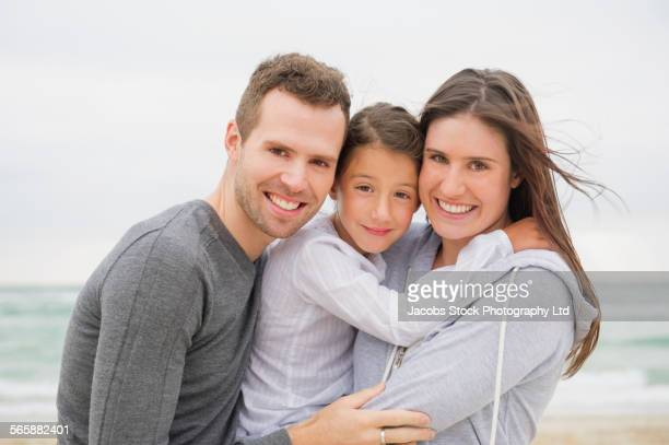 Caucasian parents hugging daughter on beach