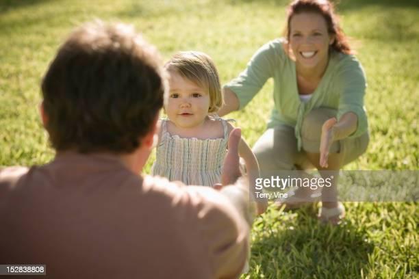 Caucasian parents teaching daughter to walk