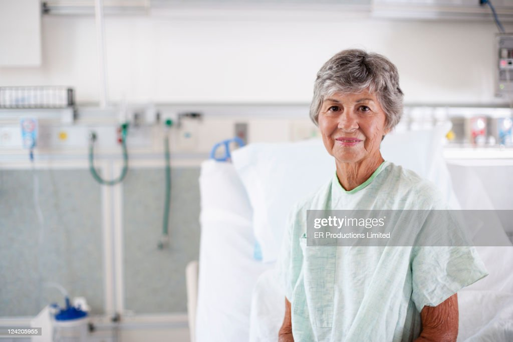 Caucasian patient in hospital gown sitting in hospital bed