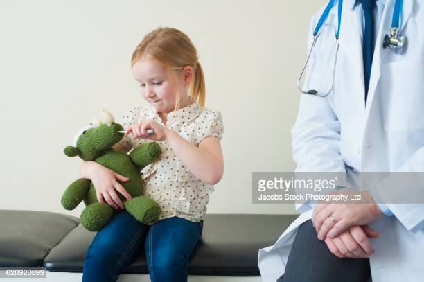 Caucasian patient playing with stuffed animal in doctors office