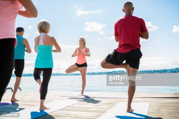 Caucasian people practicing yoga on wooden dock