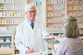 Caucasian pharmacist giving prescription to customer