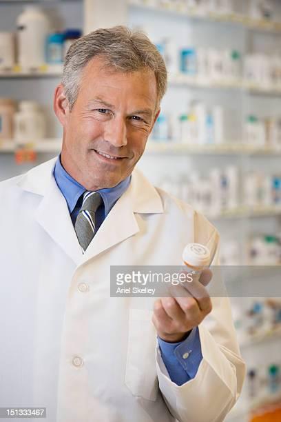Caucasian pharmacist holding medication bottle