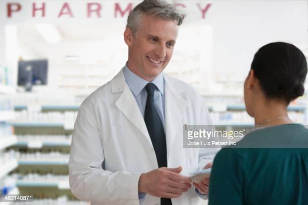 Caucasian pharmacist talking to patient