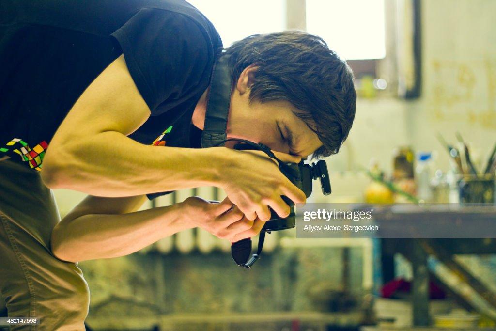 Caucasian photographer working in studio : Stock Photo