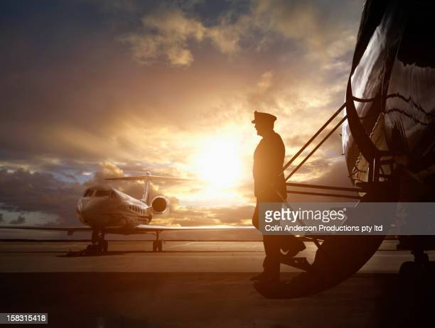 Caucasian pilot walking down steps of jet
