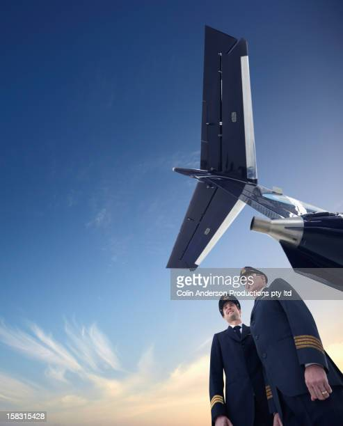 Caucasian pilots standing underneath airplane