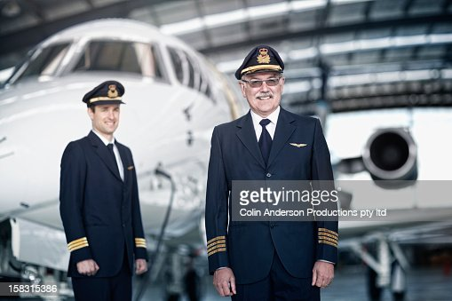 Caucasian pilots standing with airplane in hangar