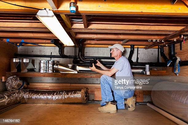 Caucasian plumber working on pipes