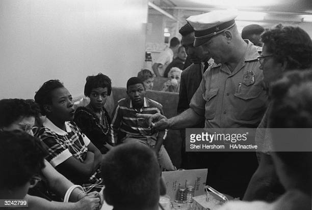 Caucasian policeman speaks with AfricanAmerican protesters during a sitin at Brown's Basement Luncheonette Oklahoma