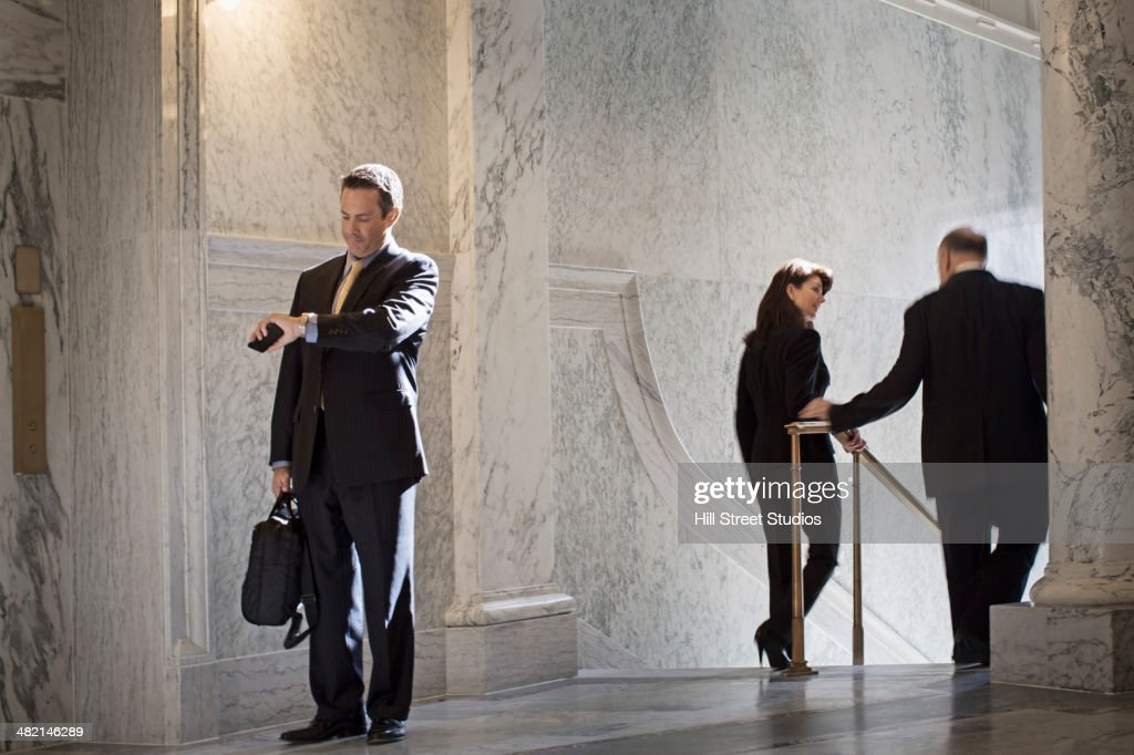 Caucasian politician checking watch in government building