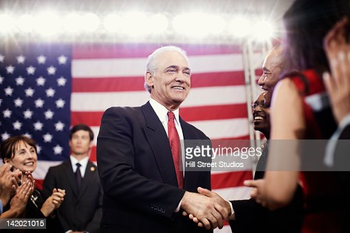 Caucasian politician shaking hands with supporters