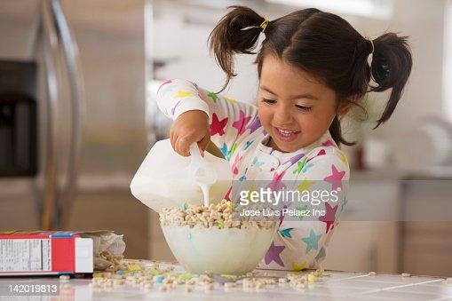Caucasian pouring milk into cereal