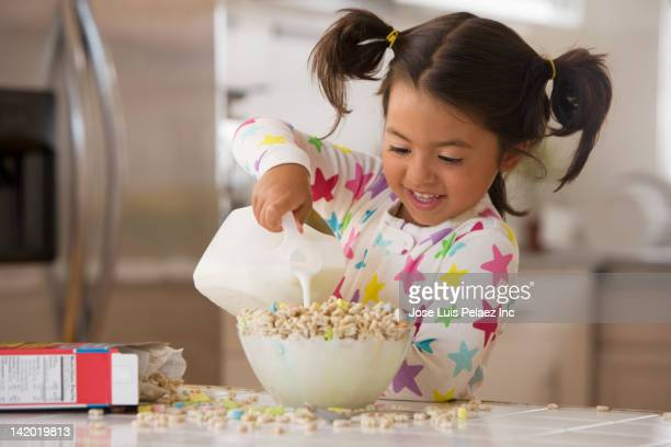 Caucasian pouring milk into cereal
