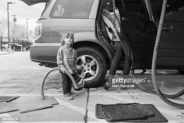 Caucasian preschooler boy helping clean car