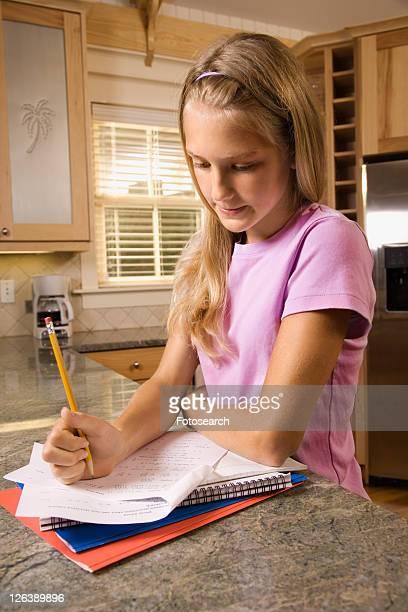 Caucasian pre-teen girl doing homework at kitchen counter.