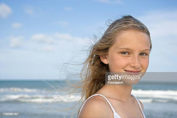 Caucasian pre-teen girl on beach looking at viewer.