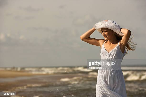 Caucasian pre-teen girl standing on beach holding hat on head.