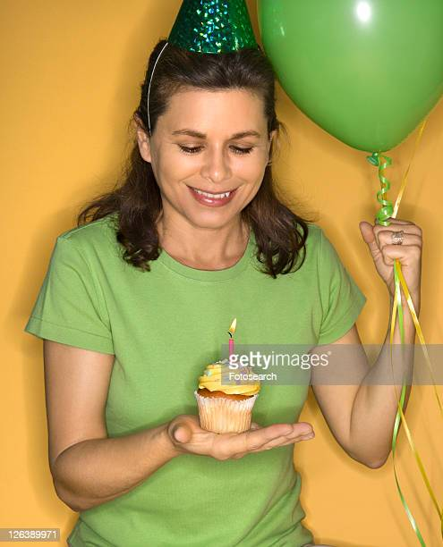 Caucasian prime adult female holding cupcake with lit candle wearing party hat.