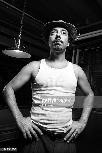 Caucasian prime adult retro male standing with hands on hips in front of pool table.