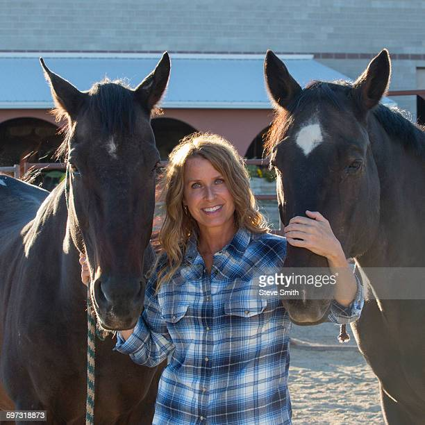 Caucasian rancher smiling with horses