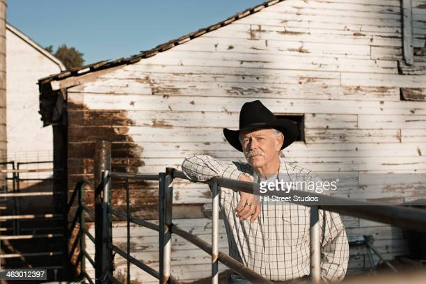 Caucasian rancher standing at gate