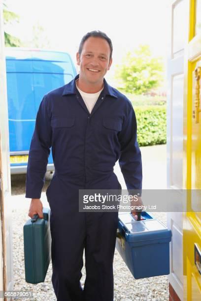 Caucasian repair man carrying tools in doorway