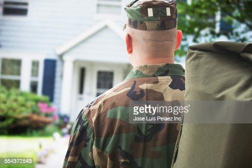 Caucasian returning soldier facing house