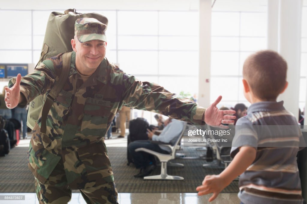 Caucasian returning soldier greeting son in airport