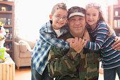 Caucasian returning soldier hugging children
