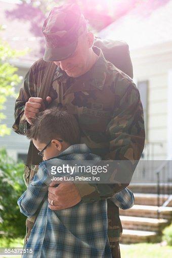 Caucasian returning soldier hugging son