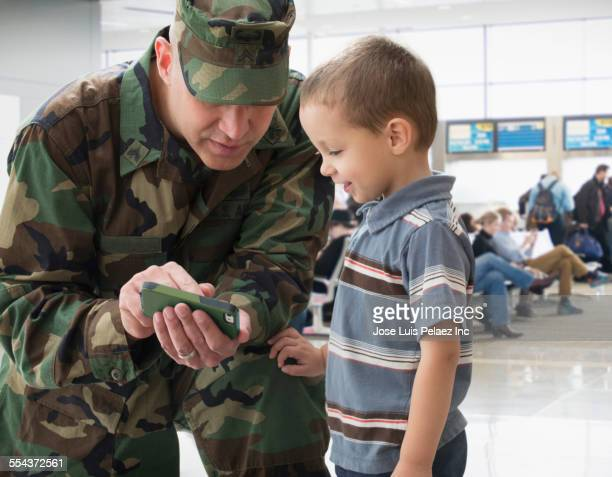 Caucasian returning soldier showing son cell phone in airport