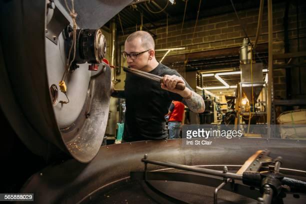 Caucasian roaster working on coffee in warehouse