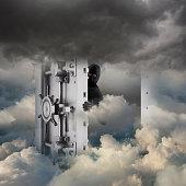 Caucasian robber opening bank vault in clouds