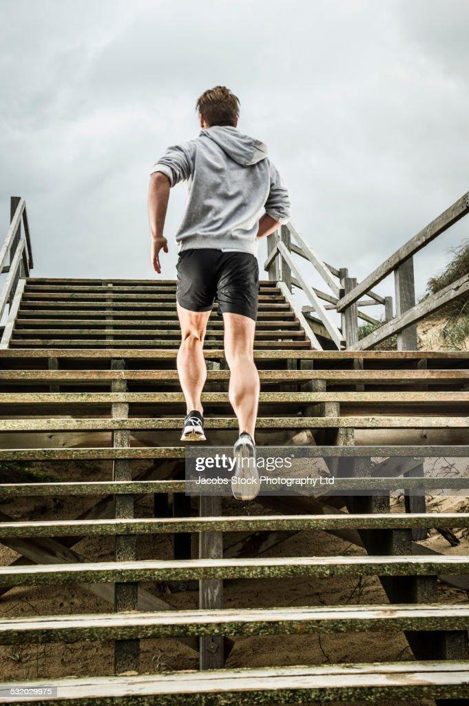 Caucasian runner climbing wooden boardwalk stairs at beach