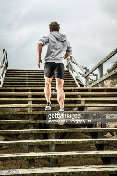 Caucasian runner climbing wooden boardwalk stairs at beach